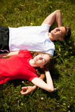 Active couple rests on a mountain peak looking on a mountain lan. Dscape Royalty Free Stock Photo