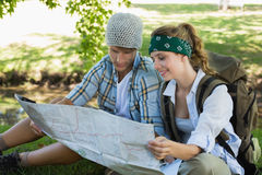 Active couple sitting down on a hike reading map Royalty Free Stock Image