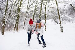 Active couple of teenagers making snowman. Happy boy and girl having fun with snow outdoors. Active couple of teenagers making snowman Stock Photography