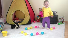 Active curly hair baby girl dancing with cute toy cat at home. stock video