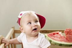 Active cute baby emotionally in the plot with a watermelon. Royalty Free Stock Images