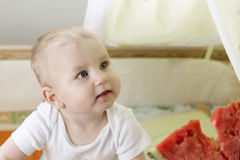 Active cute baby emotionally in the plot with a watermelon. Stock Photos