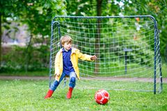 Active cute little kid boy playing soccer and football and having fun Stock Images