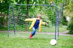 Active cute little kid boy playing soccer and football and having fun Royalty Free Stock Image