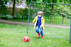 Active cute little kid boy playing soccer and football and having fun Stock Photos