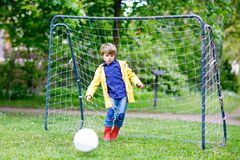 Active cute little kid boy playing soccer and football and having fun. Outdoors. Child having game on rainy day. Wearing yellow rain coat and red rubber boots Royalty Free Stock Images