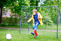 Active cute little kid boy playing soccer and football and having fun. Outdoors. Child having game on rainy day. Wearing yellow rain coat and red rubber boots Stock Images