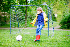 Active cute little kid boy playing soccer and football and having fun. Outdoors. Child having game on rainy day. Wearing yellow rain coat and red rubber boots Royalty Free Stock Photography