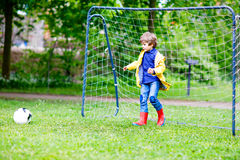 Active cute little kid boy playing soccer and football and having fun Stock Photography