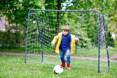 Active cute little kid boy playing soccer and football and having fun, outdoors. Child having game on rainy day. Wearing. Yellow rain coat and red rubber boots stock photos