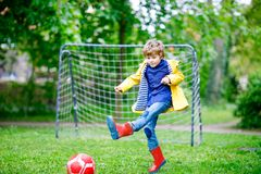 Active cute little kid boy playing soccer and football and having fun stock photo