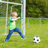Active cute little kid boy playing soccer. And football and having fun, outdoors on field. Active leisure with children on warm sunny summer day Royalty Free Stock Images