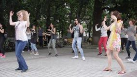 Active dances cheerful of men and women on urban plaza, people enjoy dancing on street, stock video