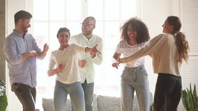 Active diverse cheerful friends dancing in living room