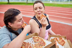 Active eaters. Happy young over-size women eating tasty and appetizing pizza after workout on stadium Stock Images