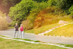 Active elderly couple enjoying Nordic walking. Favourite activity. Active nice elderly couple holding walking poles and walking along the road while taking royalty free stock photo