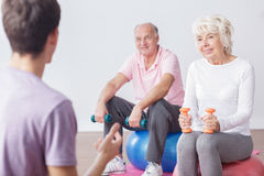 Active elderly couple and instructor. Image of active elderly couple and fitness instructor royalty free stock photos