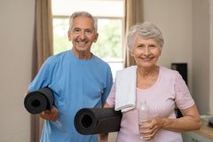 Active elderly couple ready for yoga. Active healthy senior couple holding yoga mats while going together to training. Happy fitness elderly men and women stock images