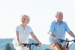 Active elderly couple riding bicycles together in the countryside. Active elderly couple wearing summer casual clothes while riding bicycles together in the royalty free stock image