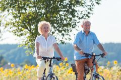 Active elderly couple riding bicycles together in the countrysid. Active elderly couple wearing summer casual clothes while riding bicycles together in the stock photos