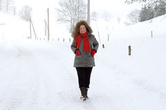 Active elderly lady in winter fashion. Standing on a rural road in pristine white fresh winter snow stock photography