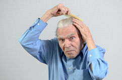 Active elderly man combing his hair with a comb. Active healthy elderly man wearing a clean blue shirt while combing his hair with a plastic comb, part of daily royalty free stock photography