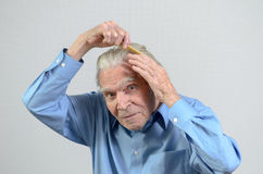 Active elderly man combing his hair with a comb. Active healthy elderly man wearing a clean blue shirt while combing his hair with a plastic comb, part of daily royalty free stock photo