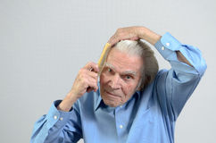 Active elderly man combing his hair with a comb. Active healthy elderly man wearing a clean blue shirt while combing his hair with a plastic comb, part of daily royalty free stock photos