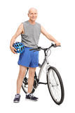 Active elderly man posing next to a bicycle Royalty Free Stock Image