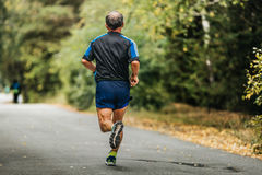 Active elderly man running. Down road in autumn Park stock images