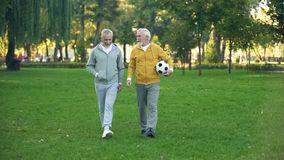 Active elderly men walking in park with football, sport hobby, health care. Stock photo royalty free stock photos