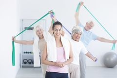 Active elderly people stretching. Using elastic tape while pretty young trainer standing in front of them royalty free stock photo