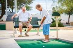 Active elderly senior couple playing miniature golf together. During the day stock photography