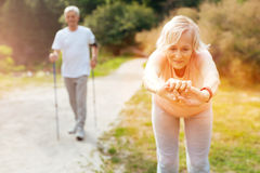 Active elderly woman doing a bending exercise. Leaning forwards. Active nice elderly women leaning forward and looking at her hands while doing a bending royalty free stock images
