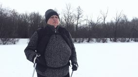 Active an elderly woman engaged in Nordic walking with sticks in the winter forest. Healthy lifestyle concept. Mature. Woman resting after exercise outdoors stock video