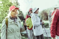 Active elderly woman hiking with her friends. Activity on pension. An active elderly women enjoying hiking with her friends royalty free stock image