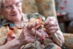 Active elderly woman. Senior woman knitting at home royalty free stock photo