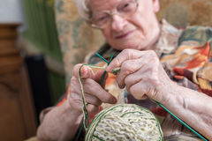 Active elderly woman. Senior woman knitting at home stock photography