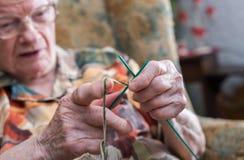 Active elderly woman. Senior woman knitting at home stock image