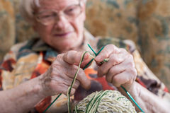 Active elderly woman. Senior woman knitting at home royalty free stock images