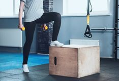 Active elderly woman training with dumbbells. No stopping any time. Close up of motivated senior lady exercising in a gym and holding dumbbells while hopping on royalty free stock image