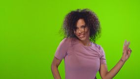 Active energized Afro woman dances and has fun feels amused and upbeat