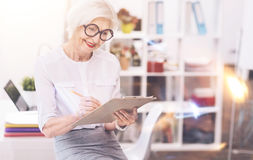 Active enterprising lady writing a schedule. Listing priorities. Accomplished classy busy woman working on her daily list of tasks while sitting on the table at Royalty Free Stock Photos