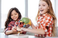 Active enthusiastic girls enjoying their time in school lab. This is fun. Bright creative pretty children attending biology class and studying human anatomy Stock Photography