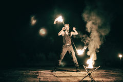 Active European guy carries out tricks for fire show night Stock Photos