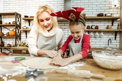 Active expressive child cutting spread dough with special tool stock photo