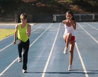 Active family. Mother and daughter exercising on a blue racetrack Royalty Free Stock Image