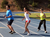 Active family. Mother, father and daughter exercising on a blue racetrack Royalty Free Stock Photos