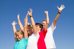 Active family. Of four arms open over blue sky background royalty free stock photography
