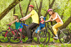 Active family on bikes riding in sunny forest. Active family on bikes riding in spring sunny forest, mother, father and two age-diverse daughters together Stock Photography